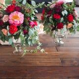 Вазы с букетами красных цветков на поле Деревянная предпосылка Стоковое Изображение RF