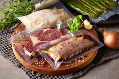 Вакуум мяса загерметизированный на каменной таблице стоковое фото