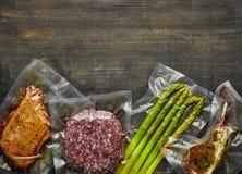 Вакуум мяса и спаржи загерметизированный на деревянном столе, космосе экземпляра, взгляде сверху стоковые фото