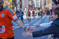 ВАЛЕНСИЯ, ИСПАНИЯ - 2-ОЕ ДЕКАБРЯ: Бегуны трясут руки с участниками на марафоне XXXVIII Валенсия 18-ого декабря 2018 в Валенсия стоковое фото