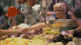 ВАЛЕНСИЯ, ИСПАНИЯ - 22-ОЕ СЕНТЯБРЯ 2018 Клиенты и поставщики на стойле плода в известном рынке Mercado центральном или центрально видеоматериал