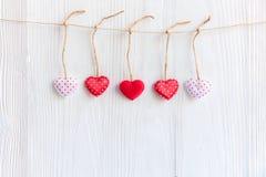 Валентайн дня s Зашитые сердца подушки гребут границу на красных и белых зажимках для белья на деревенском Стоковые Изображения