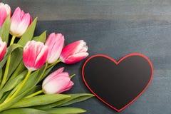 Валентайн дня s Розовые тюльпаны и пустое сердце формируют доску на голубой предпосылке, космосе экземпляра, взгляд сверху Стоковые Фотографии RF