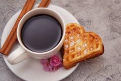 Валентайн дня s Чашка с кофе и вафлей испечет в форме сердца с циннамоном и розовым цветком на деревянном столе Стоковые Изображения