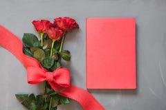 Валентайн карточки s Букет красных роз и красной тетради на сером цвете конец вверх скопируйте космос Стоковые Фотографии RF