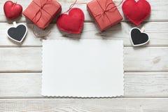 Валентайн карточки s Красное оформление, сердца, подарки, зажимка для белья с белым листом для вашего текста на белой деревянной  Стоковая Фотография RF