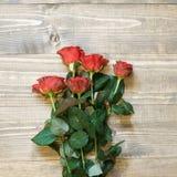 Валентайн карточки s Красные розы обернутые в бумаге на предпосылке деревянного стола Взгляд сверху Стоковые Изображения