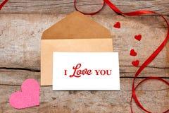 Валентинка любовного письма подняла и в конверт на деревянной предпосылке Стоковое Фото