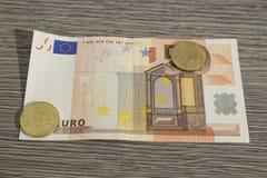 Валюта, банкнота евро 50 при 50 украшенных монеток цента на сватает стоковая фотография