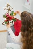 Вал украшения рождества удерживания женщины. Вид сзади Стоковое Фото