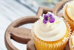 Ванильные пирожные с сахаром покрыли фиолетовые цветки на стойке торта стоковое изображение