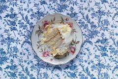 Ванильный кусок торта на точном усаживании плиты фарфора центризовал на голубой предпосылке цветка Стоковые Изображения