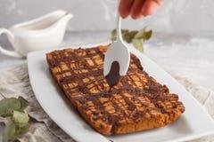 Ванильный торт aquafaba vegan с поливой шоколада в белом блюде Стоковые Фотографии RF