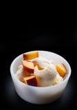 Ванильное мороженое при желтый персик изолированный на черноте Стоковое Изображение