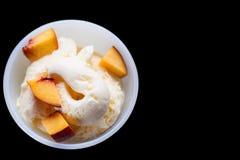 Ванильное мороженое при персик изолированный на черноте Селективный фокус Стоковые Фото