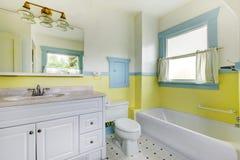 Ванная комната с желтыми стенами, белым плиточным полом, и полной ванной стоковое изображение rf