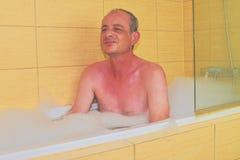 ванна имея человека Человек постаретый серединой расслабляющий в ванне вполне пены Зрелый человек в ванной комнате стоковая фотография rf