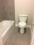 Ванна и туалет в ванной комнате нового дома стоковое изображение