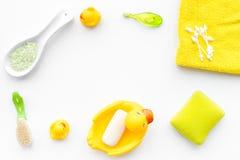 Ванна младенца установленная с желтой резиновой уткой Мыло, губка, щетки, полотенце на белом copyspace взгляд сверху предпосылки Стоковое Фото