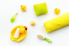 Ванна младенца установленная с желтой резиновой уткой Мыло, губка, щетки, полотенце на белом взгляд сверху предпосылки Стоковые Изображения