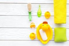 Ванна младенца установленная с желтой резиновой уткой Мыло, губка, щетки, полотенце на белом деревянном copyspace взгляд сверху п Стоковое Фото