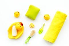 Ванна младенца установленная с желтой резиновой уткой Мыло, губка, щетки, полотенце на белом взгляд сверху предпосылки Стоковое фото RF