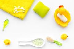 Ванна младенца установленная с желтой резиновой уткой Мыло, губка, щетки, полотенце на белом copyspace взгляд сверху предпосылки Стоковые Изображения