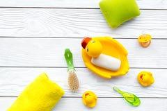 Ванна младенца установленная с желтой резиновой уткой Мыло, губка, щетки, полотенце на белом деревянном copyspace взгляд сверху п Стоковые Фотографии RF