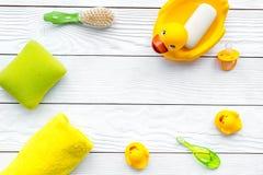 Ванна младенца установленная с желтой резиновой уткой Мыло, губка, щетки, полотенце на белом деревянном copyspace взгляд сверху п Стоковые Изображения