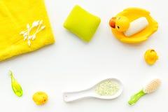 Ванна младенца установленная с желтой резиновой уткой Мыло, губка, щетки, полотенце на белом copyspace взгляд сверху предпосылки Стоковое фото RF