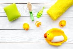 Ванна младенца установленная с желтой резиновой уткой Мыло, губка, щетки, полотенце на белом деревянном copyspace взгляд сверху п Стоковое фото RF
