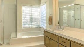 Ванна рамки панорамы и двойной блок тщеты внутри bathroom освещенного колодцем дома стоковые изображения