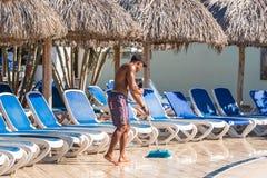 ВАРАДЕРО, MATANZAS, КУБА - 18-ОЕ МАЯ 2017: Человек подметает пол бассейном Скопируйте космос для текста Стоковое фото RF