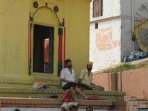 Варанаси, Уттар-Прадеш, Индия - 2-ое ноября 2009 2 кавказских люд в индийской одежде сидя на шагах Стоковые Изображения