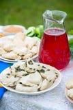 Вареники с творогом на соке плиты и клюквы в стеклянном кувшине стоя на таблице Стоковые Изображения