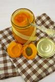 Варенье абрикоса в опарнике и свежие фрукты с листьями Стоковые Фото