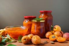 Варенье абрикоса в плите и стекле раздражает Свежие абрикосы приносить с листьями на предпосылке таблицы стоковое фото rf