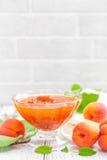 Варенье абрикоса и свежие фрукты с листьями на белом деревянном столе Стоковые Изображения RF