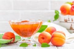Варенье абрикоса и свежие фрукты с листьями на белом деревянном столе Стоковое фото RF