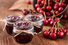 Варенье вишни на деревянной предпосылке в опарниках Стоковое Фото