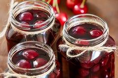 Варенье вишни на деревянной предпосылке в опарниках Стоковые Фотографии RF