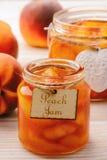 Варенье персика в стекле раздражает на белой деревянной предпосылке Стоковое фото RF
