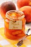 Варенье персика в стекле раздражает на белой деревянной предпосылке Стоковое Изображение RF