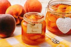 Варенье персика в стекле раздражает на белой деревянной предпосылке Стоковые Изображения