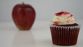 варианты еды здоровые Старты сфокусировали на красном пирожном, тогда переводят к красному яблоку сток-видео