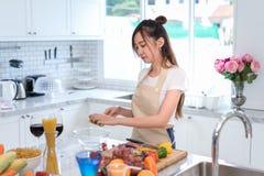 Варить азиатскую домохозяйку женщины в кухне делая здоровую еду стоковая фотография