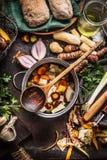 Варить бак с деревянными ложкой и овощами на деревенской предпосылке кухонного стола Домодельная здоровая еда и еда стоковые изображения