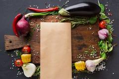 Варить бумагу, пергамент на деревянном столе с границей овощей на темной предпосылке Стоковое фото RF