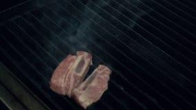 Варить вождь кладет сырую часть мяса на горячий куря гриль с огнем под использованием пинцета металла, конца вверх по замедленном сток-видео
