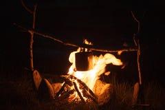 Варить еду лагеря в котле на открытом огне на ноче Стоковое Фото